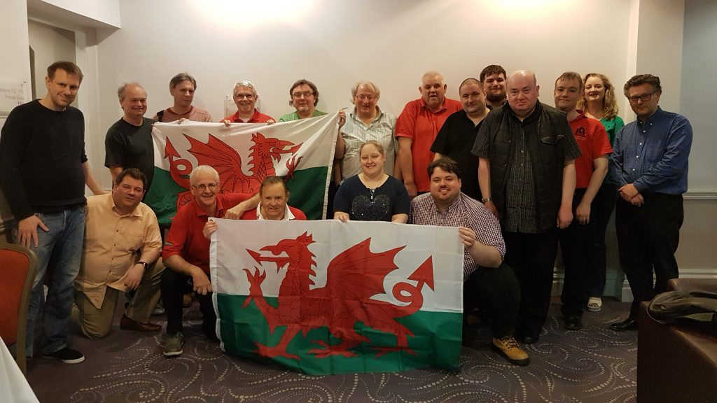 Quizzers from the Wales team at the 2018 Celtic Nations Quizzing Championships holding Welsh flags